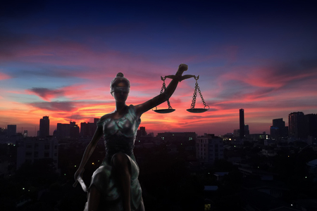 equidad: Silhouette of Lady Justice and city in dawn time