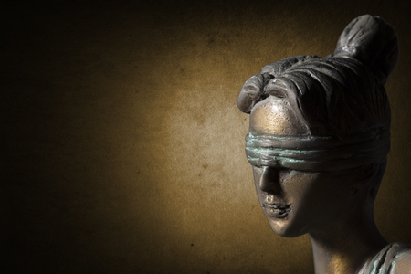 Face of Lady Justice on dark golden background
