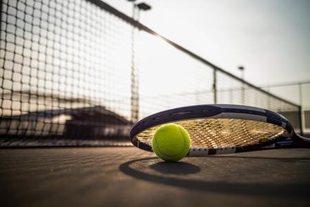 테니스 공 및 태양 빛 아래 하드 코트에 라켓