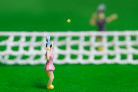 Tennis player figurines playing tennis on grass court Stock Photo