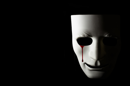 White mask and bloody tear on black background (Concept of sorrow and Halloween) Stock Photo