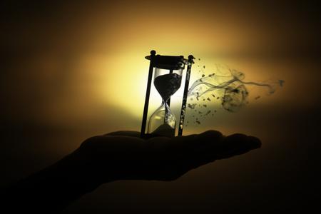 砂時計シルエットは手に最後の日光 (時間を無駄の概念) の懐中時計を崩壊します。 の写真素材・画像素材 Image 84470691.