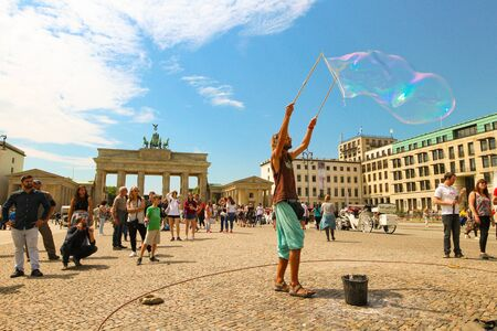 Berlin, Germany - July 13, 2018: Street entertainer playing colorful soap bubbles among the crowd in front of the Brandenburg Gate in Berlin.