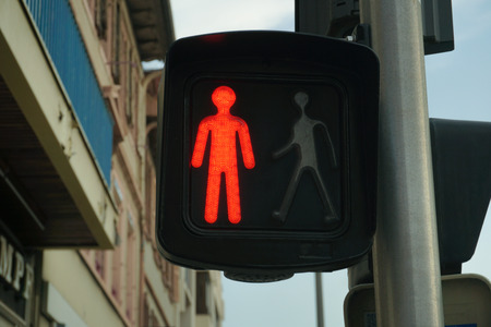 Traffic light with red sign for walkers to stop walking