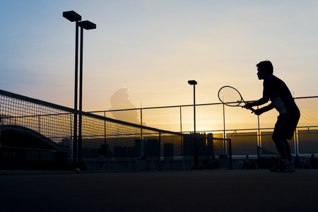 Silhouette man preparing for tennis ball at tennis court in the dawn time