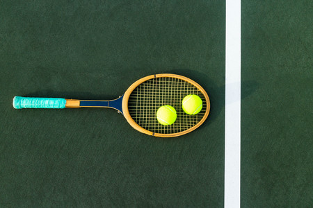 Vintage tennis racket with two tennis balls on hard court