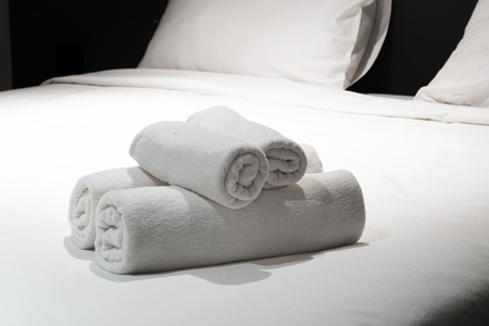 Stacks of role white towel on bed Stockfoto - 116524863