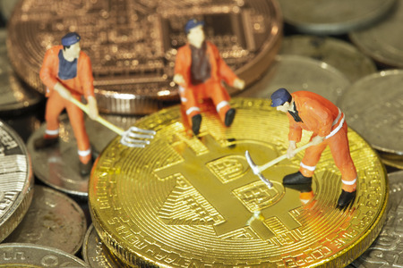 Miner figures working on group of bitcoins. Macro. Concept of cryptocurrency mining