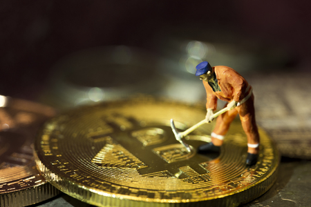Miner figure working on group of bitcoins. Macro. Concept of cryptocurrency mining