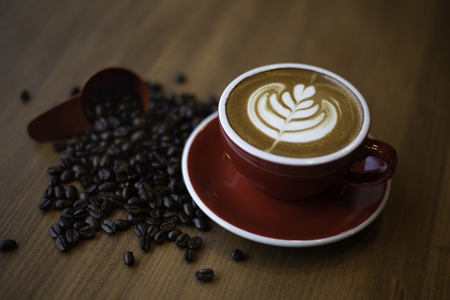 Tulip latte art with coffee beans on wooden table Stockfoto