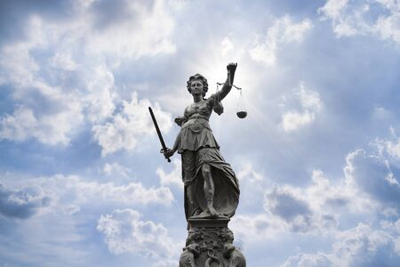 Justilia, Lady Justice or Themis and blue sky Stock Photo
