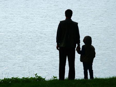 kind silhouet: Man en kind silhouet op het meer in avond Stockfoto
