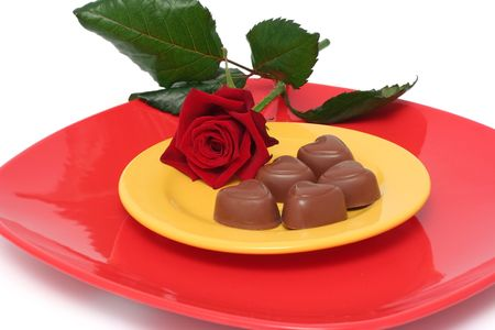 Chocolate heart on plates and a rose photo