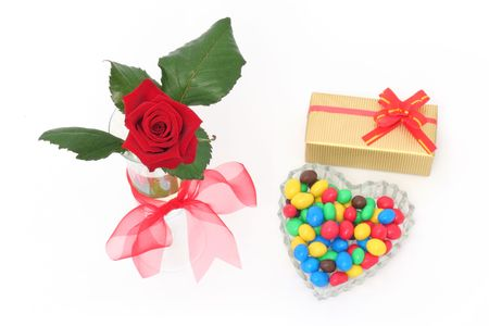 Red rose, gift and colorful candy drops photo