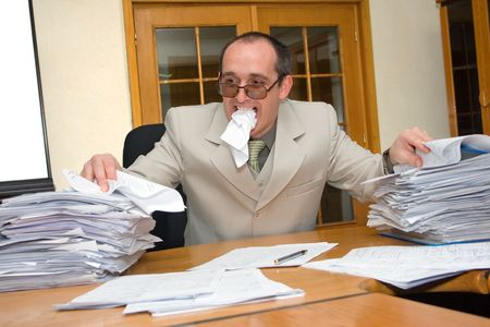 tiresome: Distressed businessman eating the paperwork