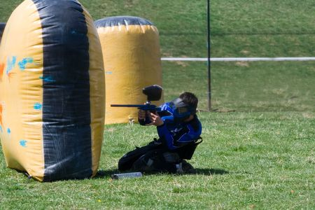 defending: Paintball player on the ground, defending the position Stock Photo