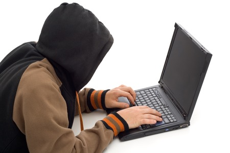 Hacker in the front of a laptop computer Stock Photo