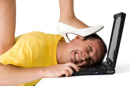 Woman legs stepping on the man's head while he is working on a laptop Stock Photo - 1512084