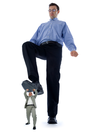tall man: Big businessman stepping on a small but strong fellow businessman. Conceptual view of how big companies want to destroy the little ones.