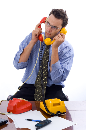 pessoas: Busy businessman talking on two telephones in the same time