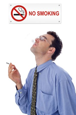 dissent: Man smoking cigarette under a NO SMOKING plate Stock Photo