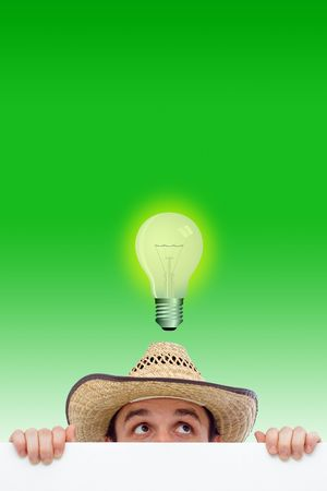 Man behind a white wall (paper) on green background, he has an idea (represented by a bulb illustration) photo