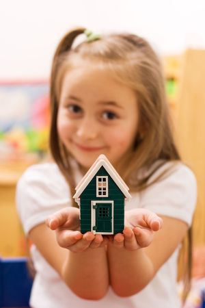 Girl showing her wish to their parents: a new home [focus on the house] Stock Photo - 2324375