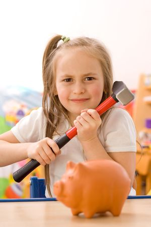 Angry girl ready to break the piggy bank with hammer [focus on the girl] photo