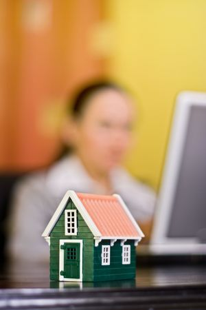 Person working in office, a miniature house in front represents his target Stock Photo - 2324388