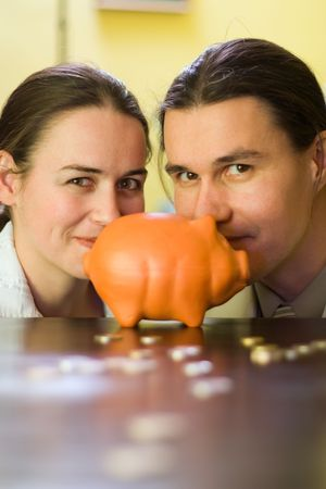Couple behind piggy bank and some coins in front Stock Photo - 2324391