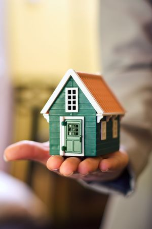 Real estate business - woman holding a miniature house in hand 스톡 콘텐츠