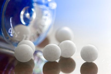 Extreme macro of homeopathic medications - small white balls and the container