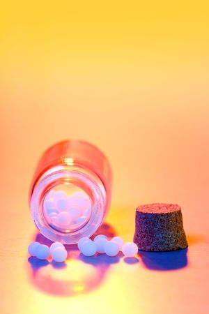 dilute: Close view of homeopathic medication in colored light - small white balls in glass bottle