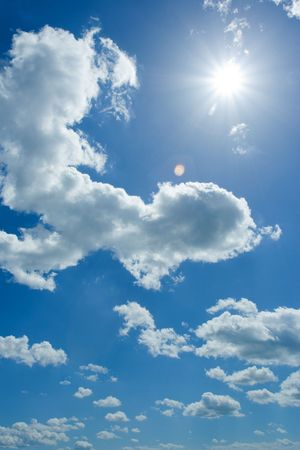 Cumulus clouds and the sparkling sun on the blue summer sky Stock Photo - 3242982
