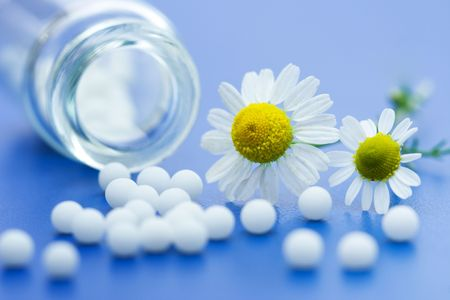 Chamomile flower and homeopathic medication on blue surface