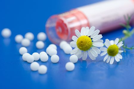 placebo: Chamomile flower and homeopathic medication on blue surface