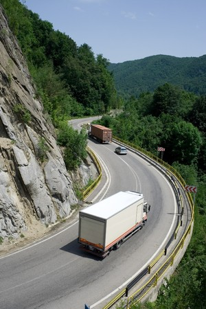 logging truck: Trucks delivering cargo on mountain road Stock Photo