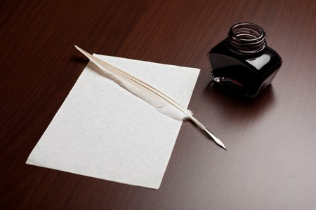 Ink, quill and an empty page on brown desk Stock Photo - 4328512