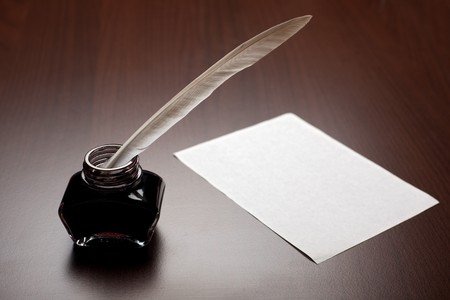Ink, quill and an empty page on brown desk photo