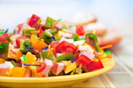 Party food, ham, salami cheese and vegetables on plastic sticks photo