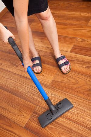 Woman cleaning the floor with vacuum cleaner