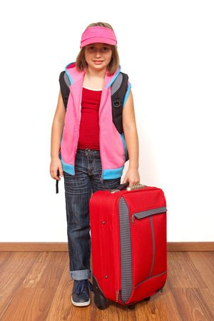 Little girl ready to travel with big red luggage photo