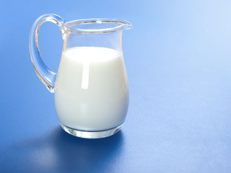 One liter milk in glass jug, on blue surface Stock Photo - 6824286