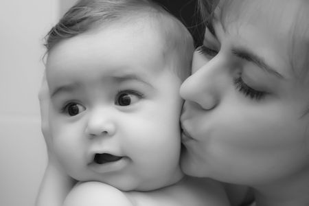 Mother giving a kiss to her little happy baby baby boy; black and white Stock Photo