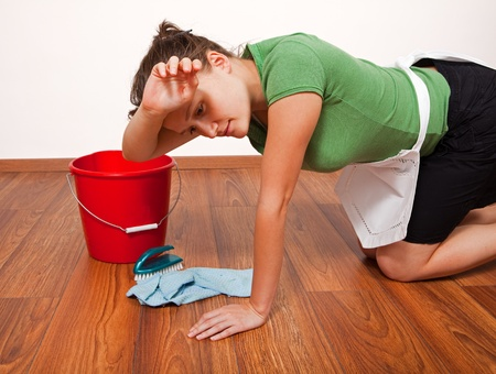 Wood work: Woman getting tired after hard work of floor cleaning Stock Photo