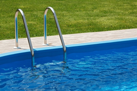 pool side: Blue pool with fresh and clean water and green grass
