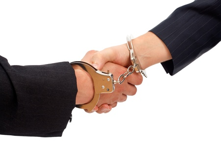 linked hands: Forced handshake between two men, their hands linked with handcuffs