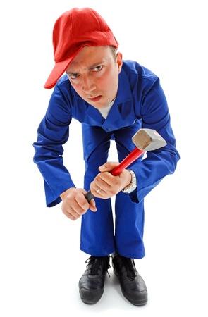 Awkward dangerous repairman with big hammer; looking down seriously photo