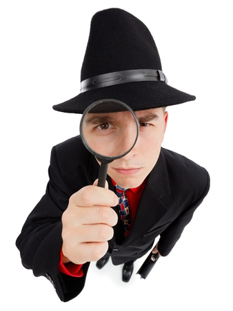 Wide angle top view of a young detective, looking up through magnifier photo