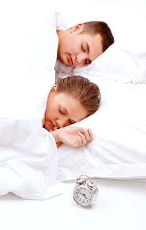 Sleeping young couple and alarm clock near the bed Stock Photo - 8922849